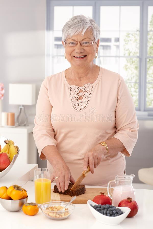 Mature woman preparing healthy breakfast. Happy mature woman preparing healthy breakfast, slicing brown bread, looking at camera royalty free stock photo