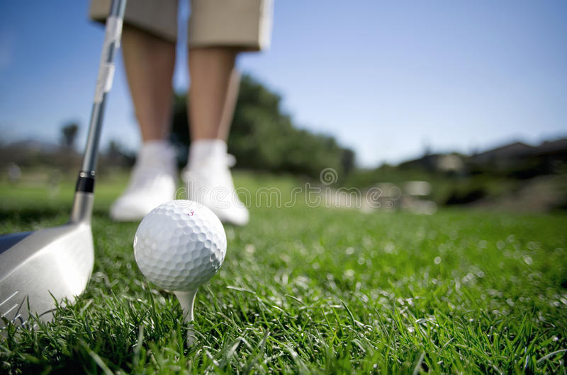 Mature woman preparing to tee off with driver on golf course, close-up, low section, focus on golf ball in foreground (surface lev stock photography