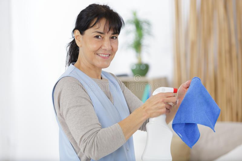 Mature woman in protective gloves smiling and wiping dust stock photos