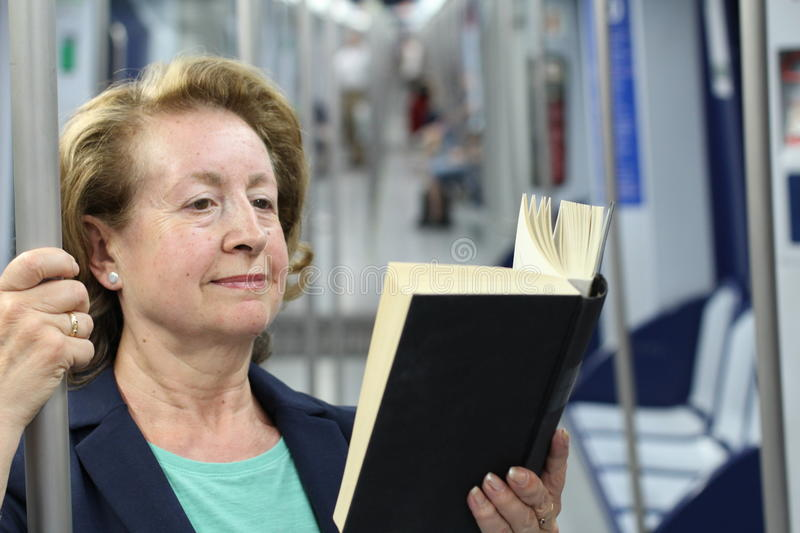 Mature woman reading book in subway train at metro stock images