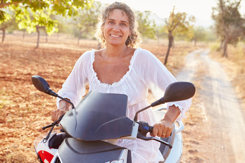 Mature Woman Riding Motor Scooter Along Country Road stock image