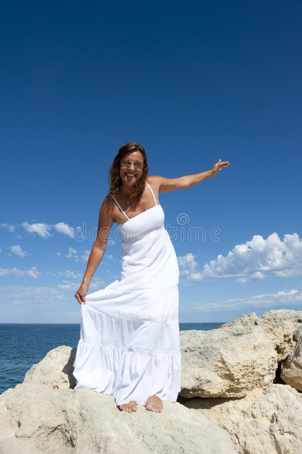 Mature Woman in Romantic White Dress at Ocean stock photography