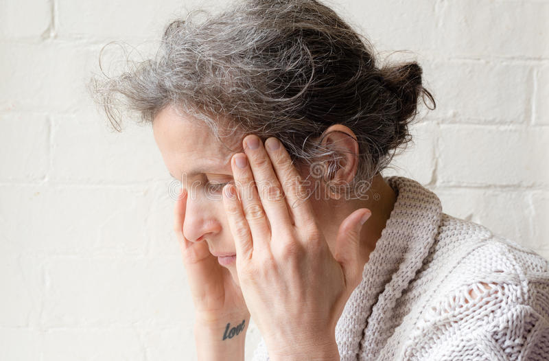 Mature woman rubbing temples stock image