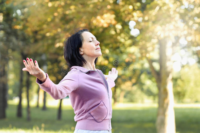 Mature woman runner taking a rest after running in the park royalty free stock photos