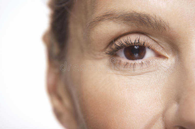 Mature Woman's Eye. Detail shot of mature woman's eye over white background stock photos