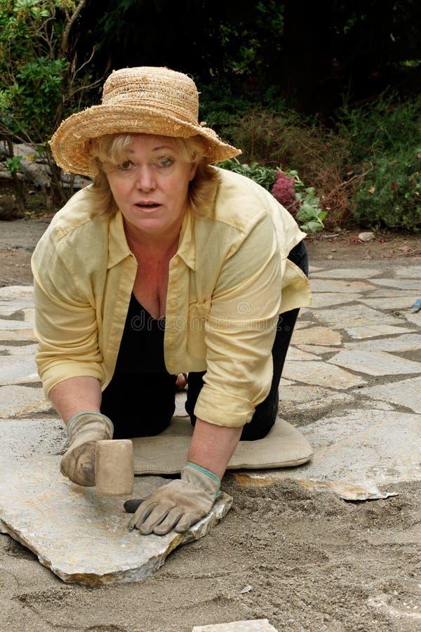 Mature woman setting pavers