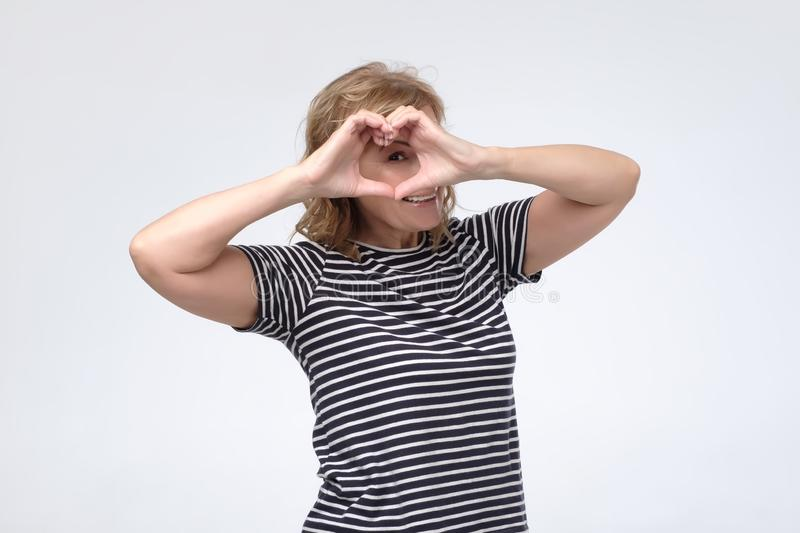 Mature woman shows heart sign with help of her hands. Love, heart shape, peace. Mature woman shows heart sign with help of her hands. Studio shot royalty free stock images