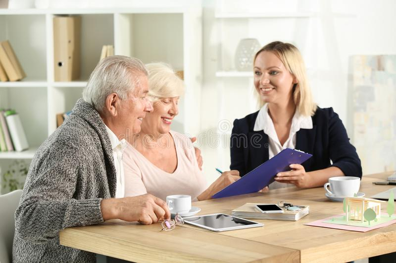 Mature woman signing a a mortgage loan agreement in office of real estate agent. Mature women signing a a mortgage loan agreement in office of real estate agent stock photos