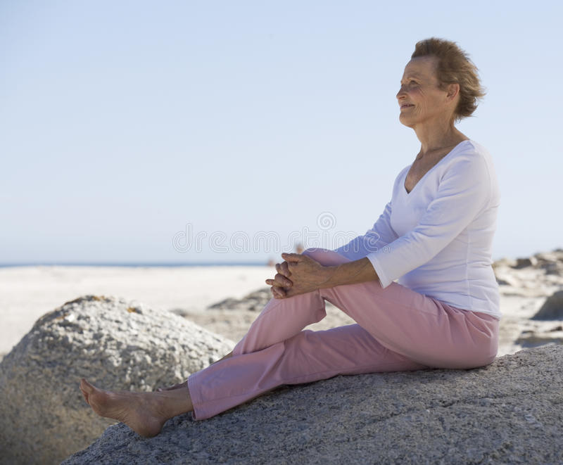 A mature woman sitting on a beach royalty free stock photo
