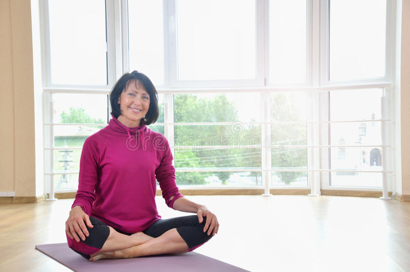 Mature woman sitting on the floor in lotus position. Healthy fitness concept with active lifestyle royalty free stock image
