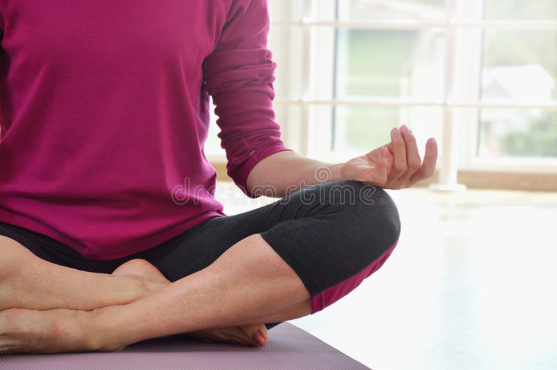 Mature woman sitting on the floor in lotus position. Healthy fitness concept with active lifestyle. Close up stock image