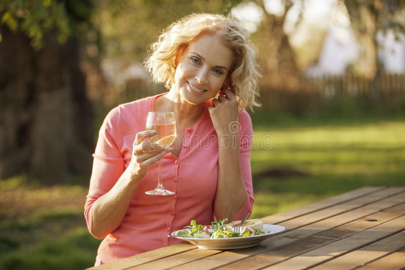 A mature woman sitting at a garden bench eating a meal royalty free stock photography