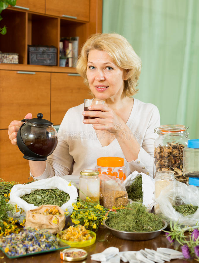 Mature Woman Sitting At  Table With Herbs Stock Photo