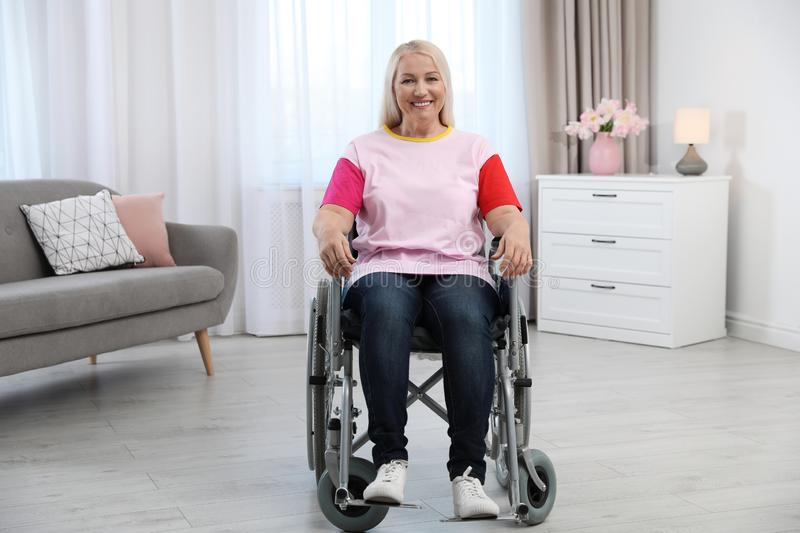 Mature woman sitting in wheelchair stock photography