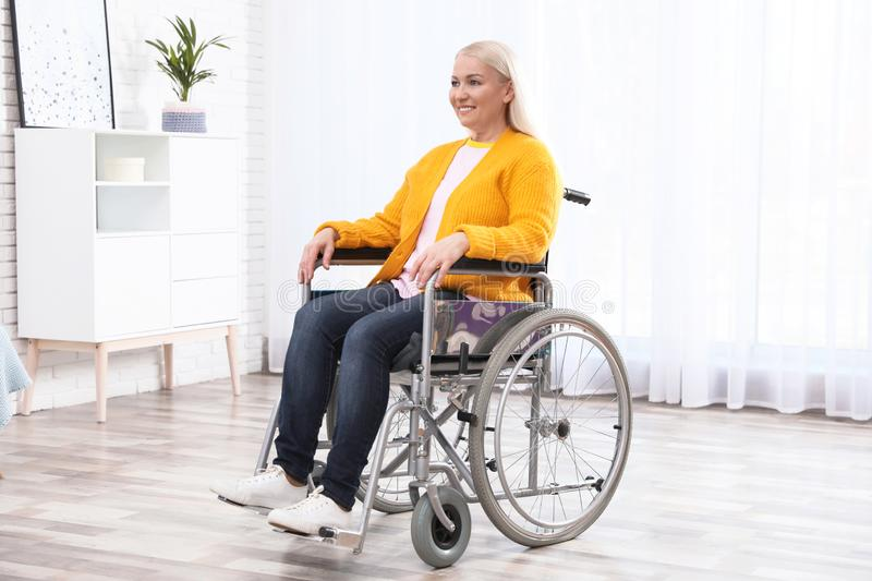 Mature woman sitting in wheelchair stock photo