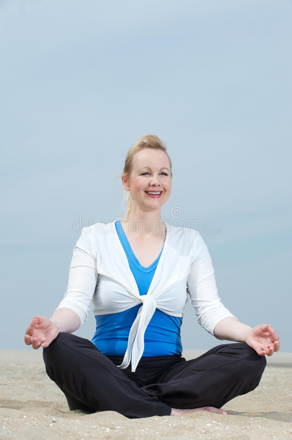 Download Mature Woman Sitting In Yoga Position At Beach Stock Image - Image: 32625971