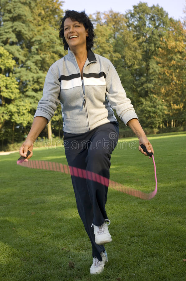 A mature woman skipping. royalty free stock photography