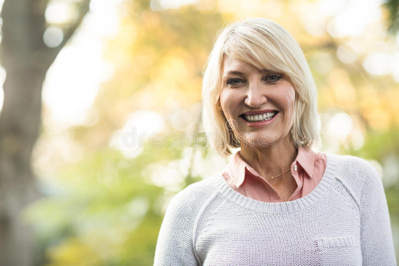 Mature woman smiling while standing in forest stock images
