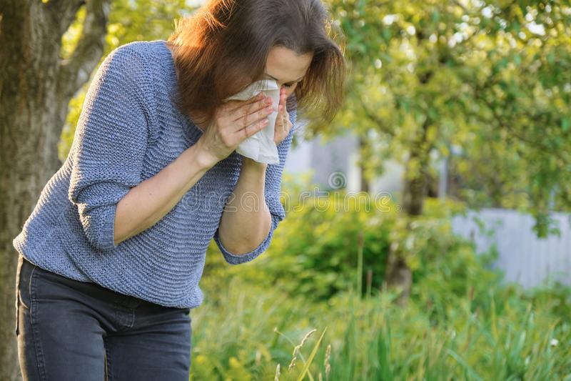 Mature woman sneezing in handkerchief, allergy to pollen, colds stock images