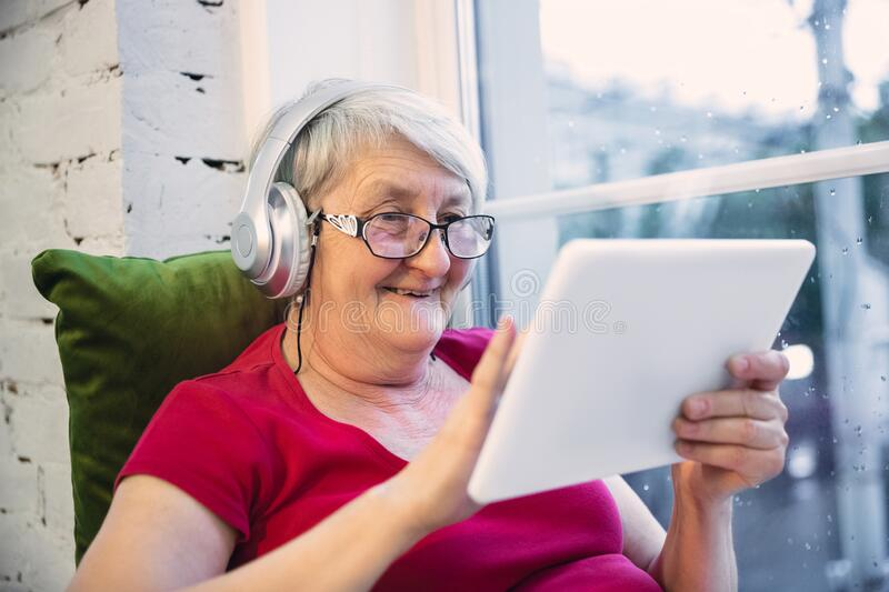 Mature woman spending time being quarantined - caucasian woman using modern gadgets, drinking tea stock images