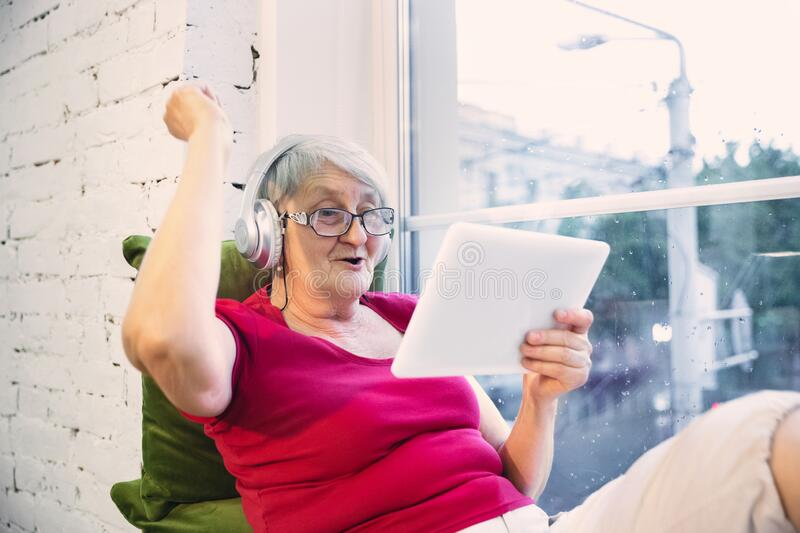 Mature woman spending time being quarantined - caucasian woman using modern gadgets, drinking tea royalty free stock photos