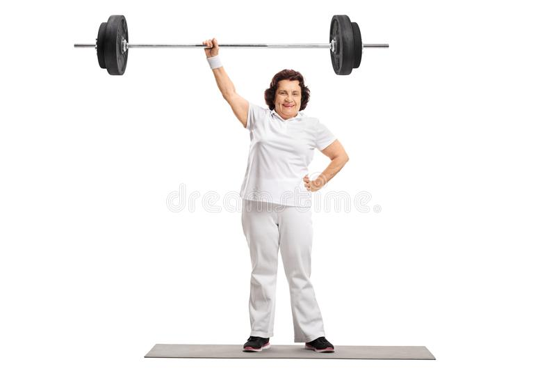Mature woman on standing on an exercise mat and lifting a barbel royalty free stock images
