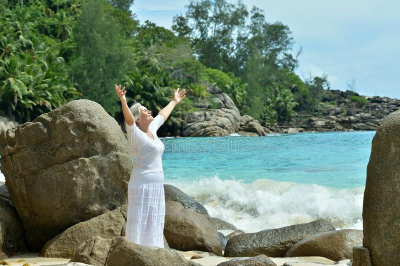Mature woman standing at sandy beach with rocks stock photography