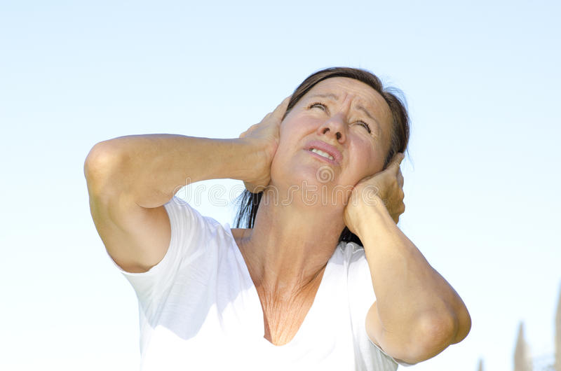 Mature woman stressed by noise stock images
