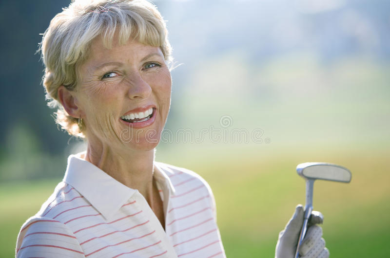 Mature woman in striped polo shirt and golf glove standing on golf course, holding putter, laughing, close-up, portrait royalty free stock image