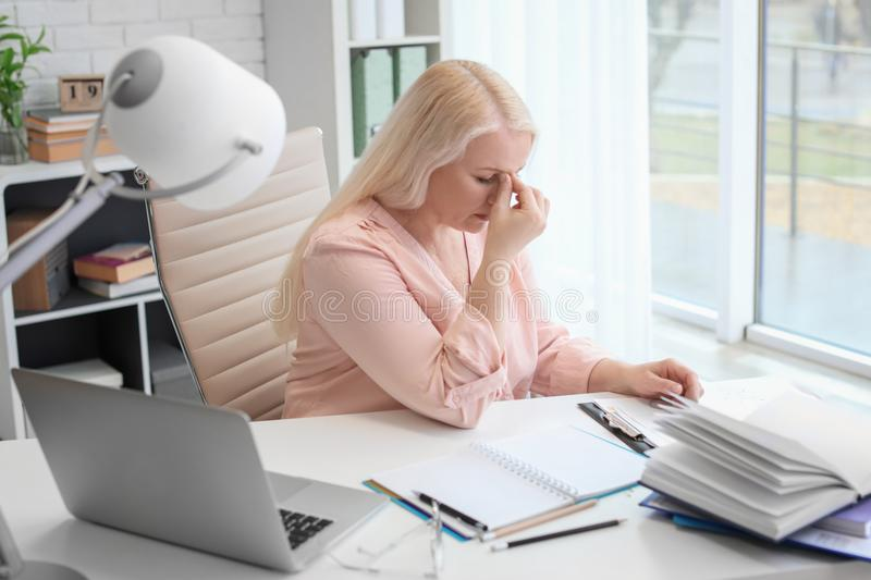 Mature woman suffering from headache while sitting at table stock photo