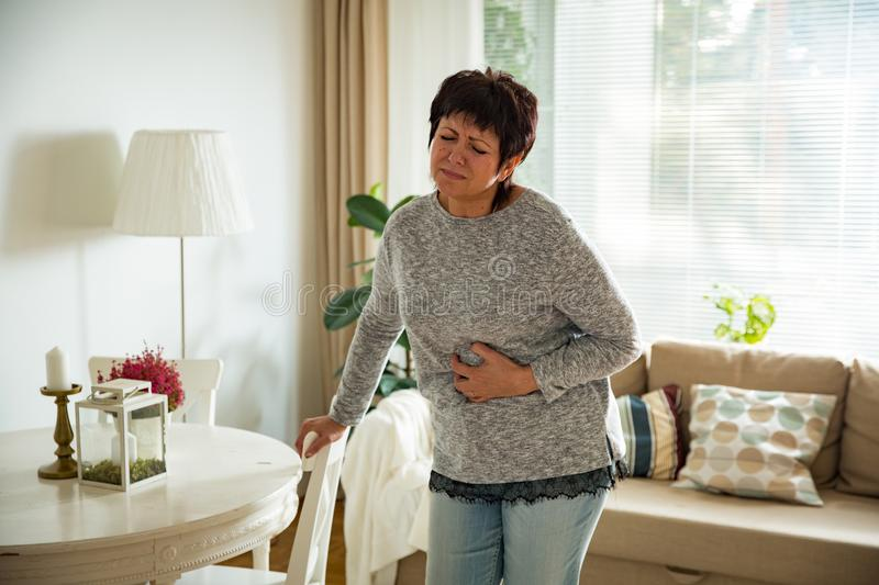 Mature woman suffering from stomach ache royalty free stock photography