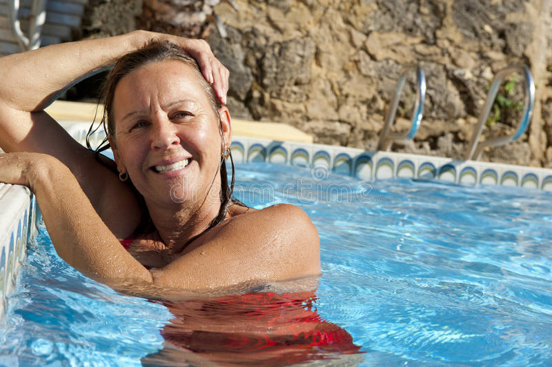 Mature woman in swimming pool royalty free stock photography