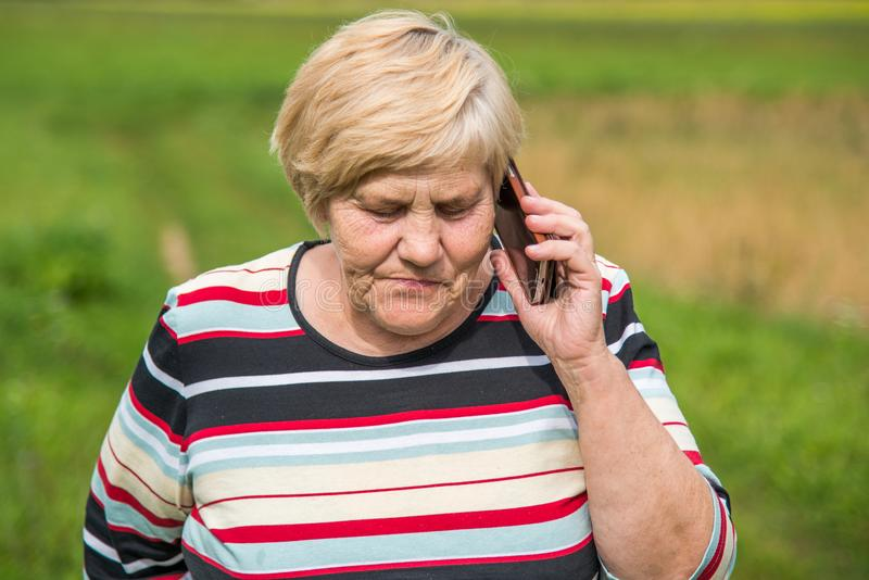 Woman talking on a phone outdoors park. Mature woman talking on a phone in nature summer royalty free stock photo