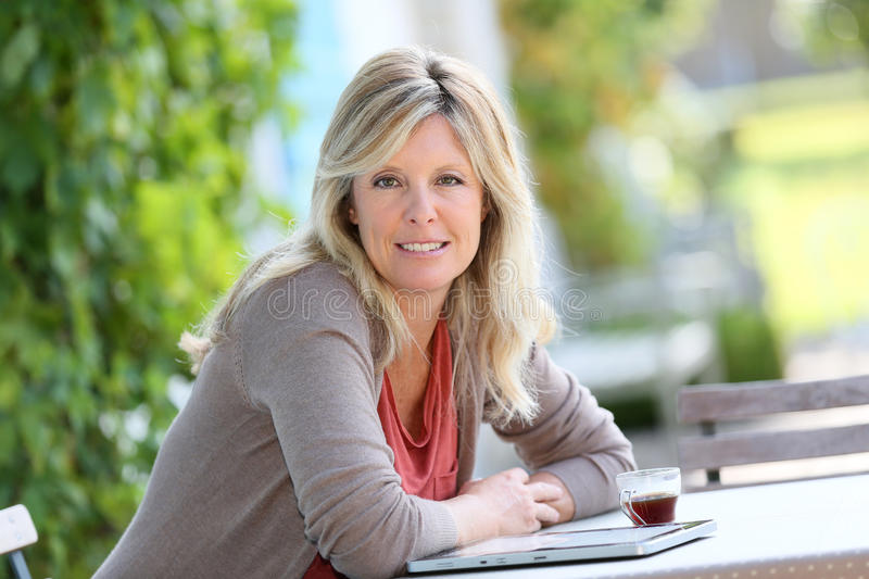 Mature woman in terrace with tablet stock photos