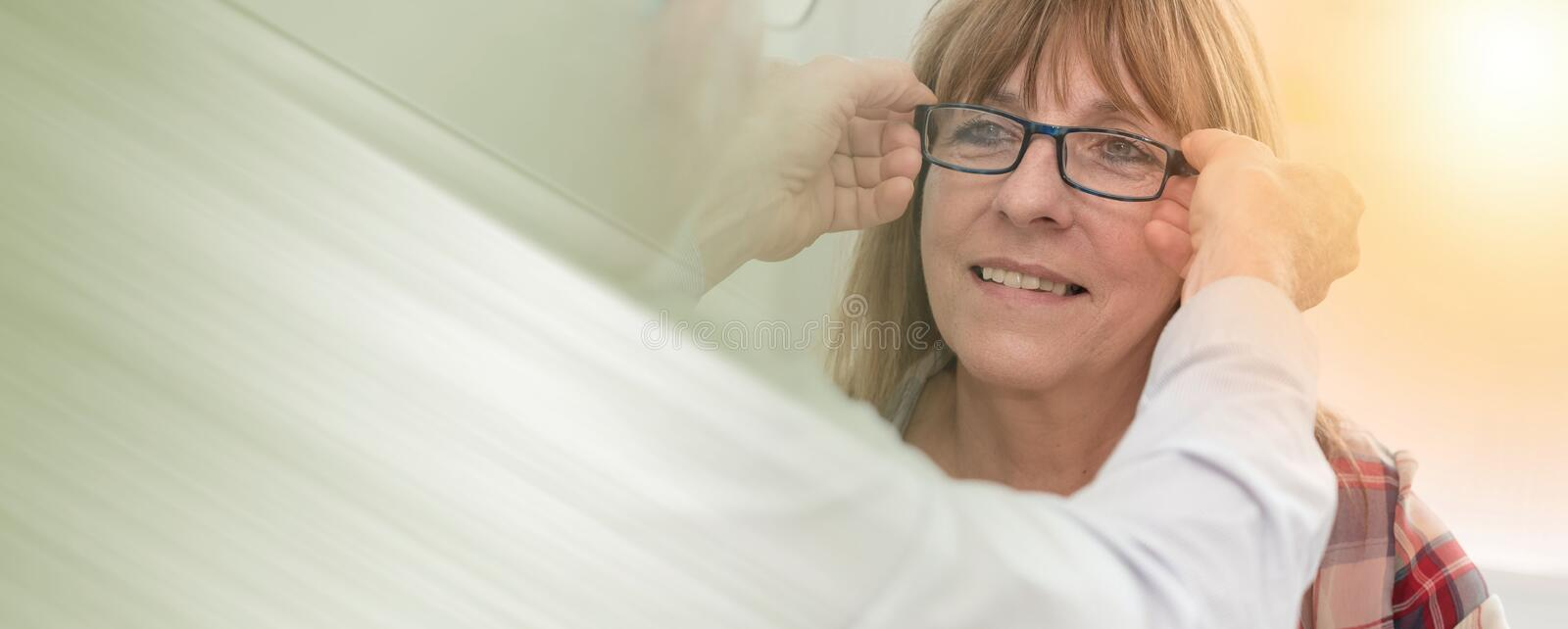 Mature woman testing new eyeglasses, light effect; panoramic banner royalty free stock images
