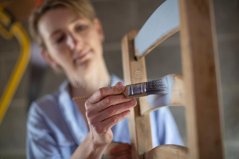 Mature Woman Upcycling Furniture In Workshop At Home  Painting Wooden Chair. Mature Woman Upcycling Furniture In Workshop At Home Painting Wooden Chair royalty free stock photos