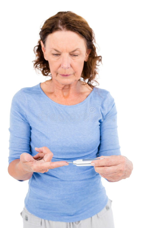 Mature woman using blood glucose monitor. Against white background stock photography