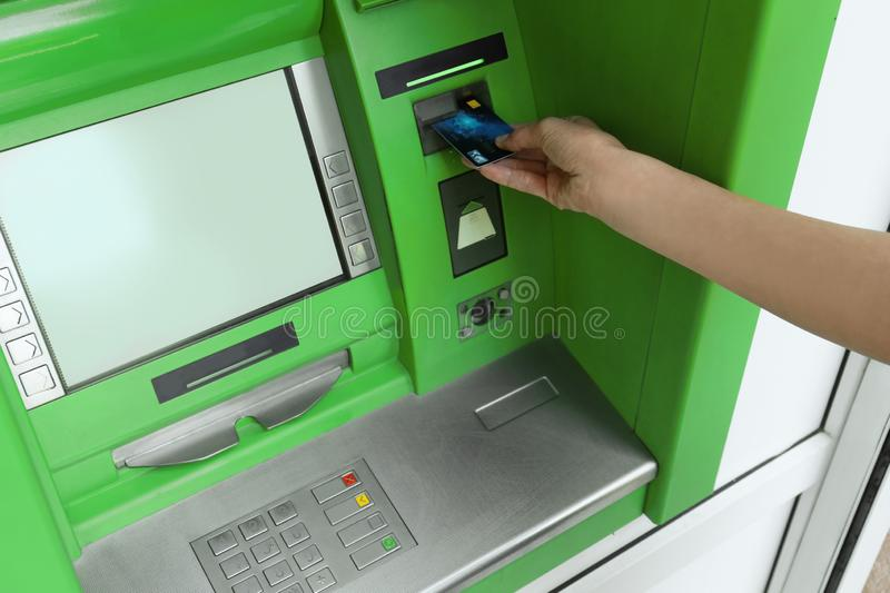 Mature woman using cash machine for  withdrawal, closeup. Mature woman using cash machine for money withdrawal, closeup royalty free stock photo