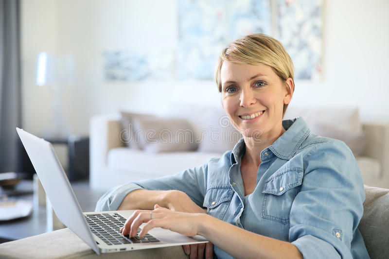 Mature woman using laptop at home stock photography