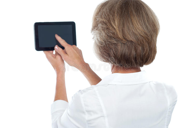 Mature woman using tablet, from back. stock image