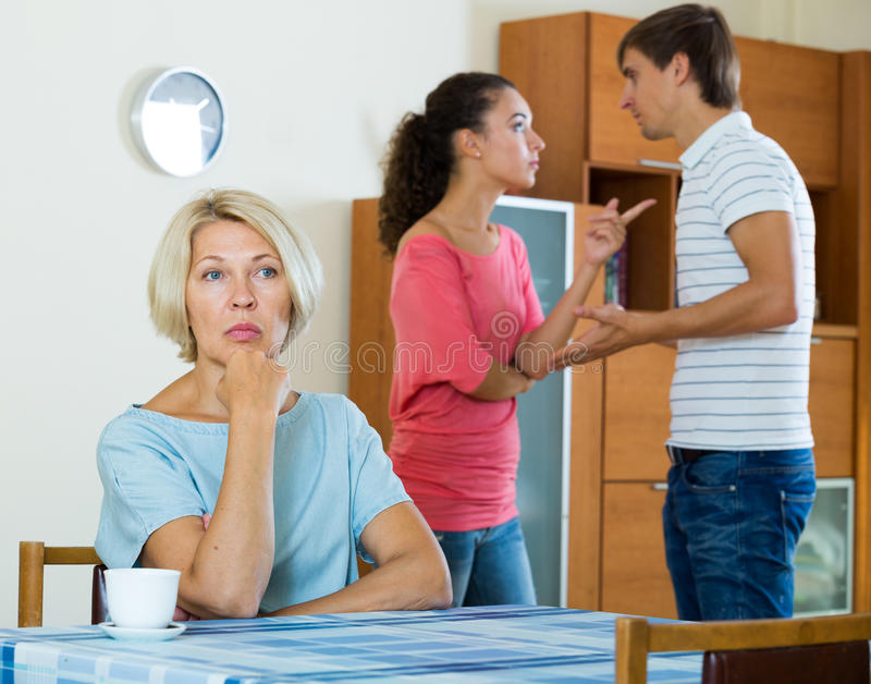 Mature woman watching young family couple quarrel at home royalty free stock image