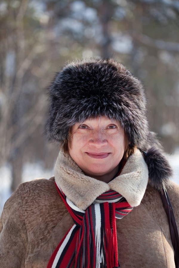 Mature woman wearing fur cap stock images
