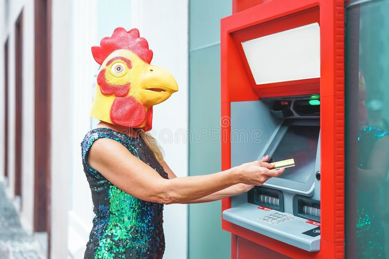 Mature woman wearing mask withdraw money from bank cash machine with debit card - Surreal image of half human and animal stock photo