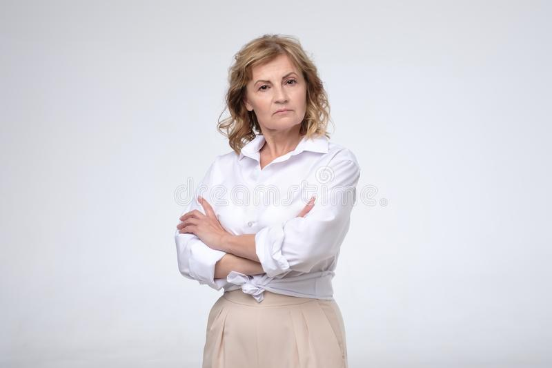 Mature woman wearing white shirt standing with folded arms looking at the camera stock photography