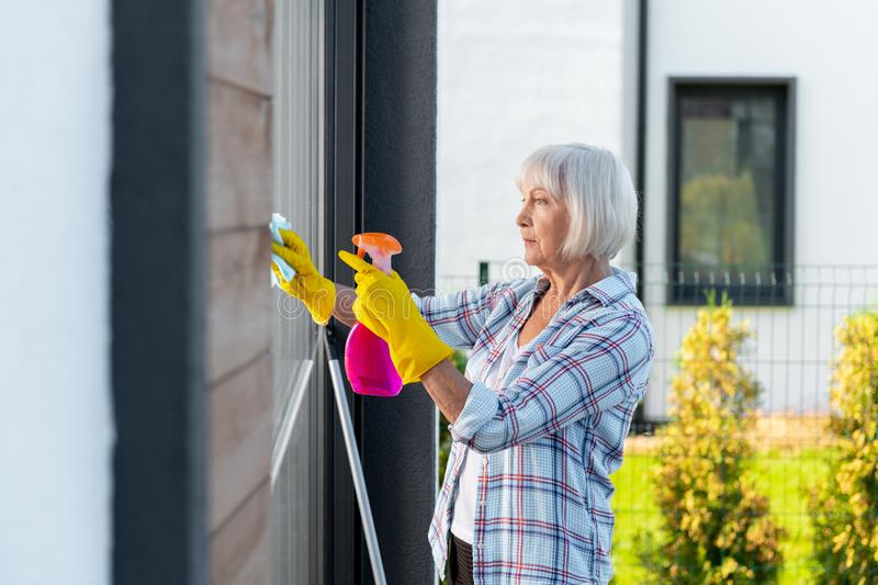 Mature woman wearing yellow gloves washing windows of summer house stock photography