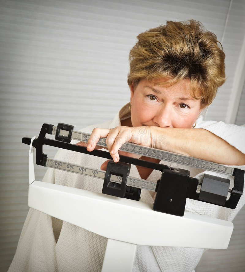 Mature Woman on Weight Scale. Closeup of a pretty but worried mature woman weighing herself on a medical scale stock photos