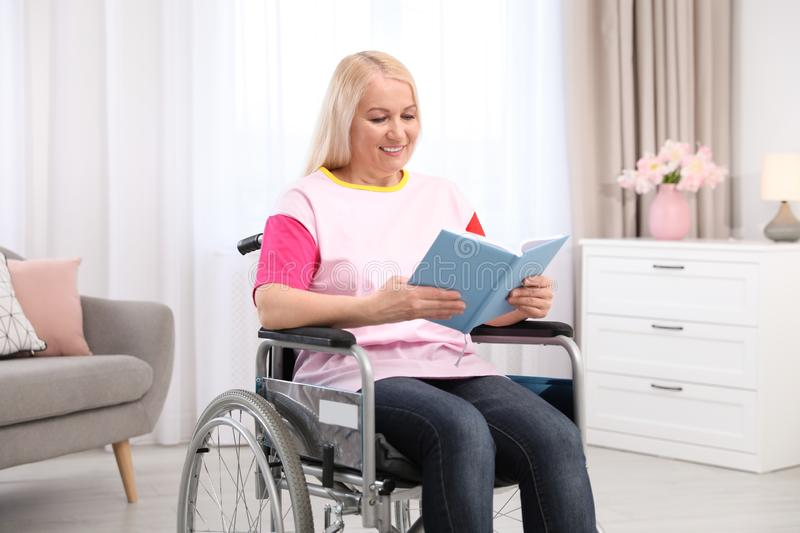 Mature woman in wheelchair with book stock photography