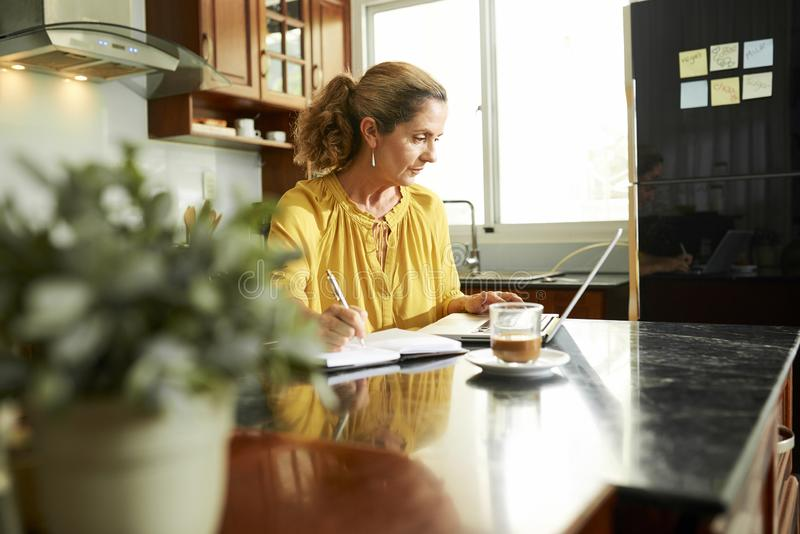 Mature woman working on laptop and taking notes stock photo