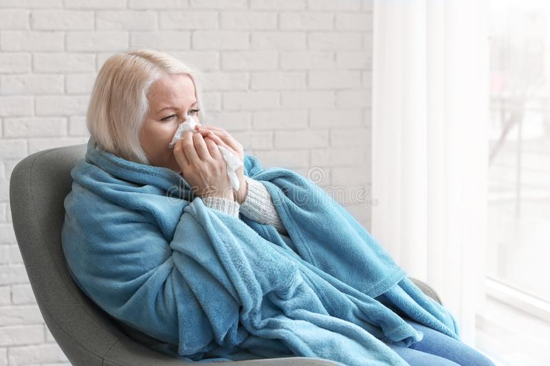 Mature woman wrapped in blanket suffering from cold stock photography