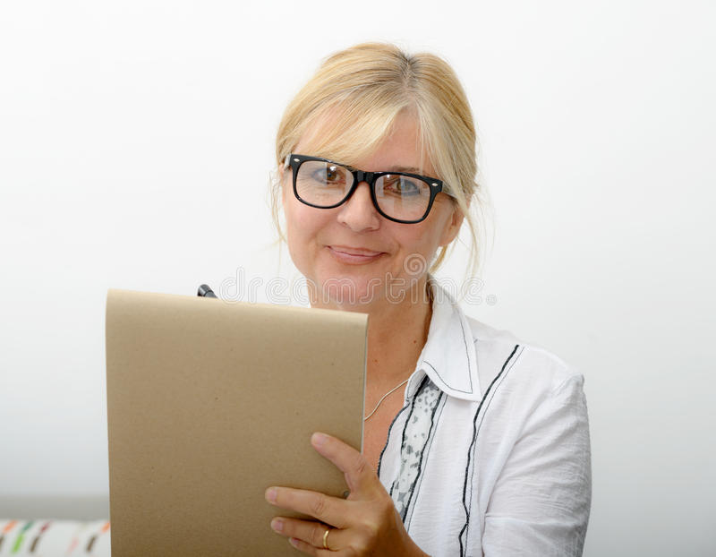 Mature woman writing on a notebook royalty free stock images